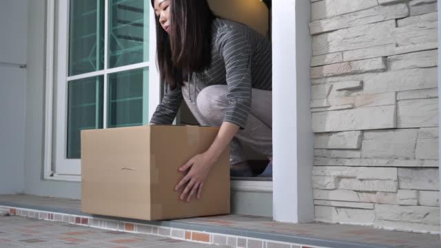 家の配達小包 - 配送、物流配達員 - 玄関のドア点の映像素材/bロール