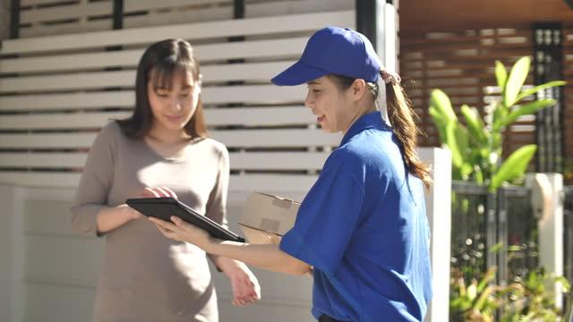 vídeos de stock, filmes e b-roll de entregador carregando caixas de papel encomenda entrega para clientes mulheres - portable information device