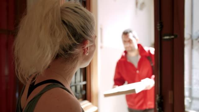 vídeos de stock, filmes e b-roll de pessoa da entrega que dá a caixa da pizza à mulher na entrada - bolsa objeto manufaturado