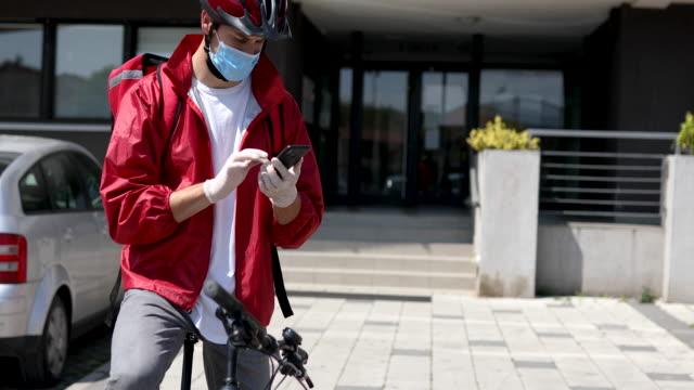 vídeos y material grabado en eventos de stock de el repartidor deja un sms a un cliente que su pedido está en su puerta principal debido a la seguridad durante la pandemia de coronavirus - navegación