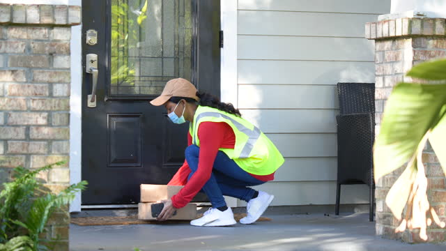delivery person leaving boxes at front door wearing mask - porch stock videos & royalty-free footage