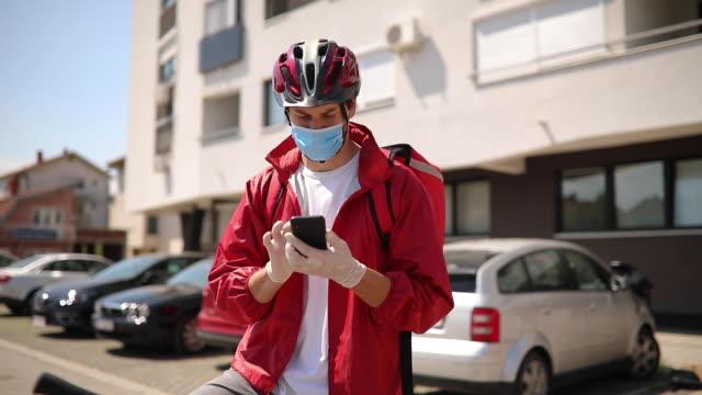 スマートフォンを使用して顧客の住所を見つける配達員 - 位置点の映像素材/bロール