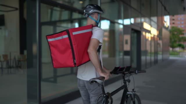 自転車で配達の準備をしている配達員 - pushing点の映像素材/bロール