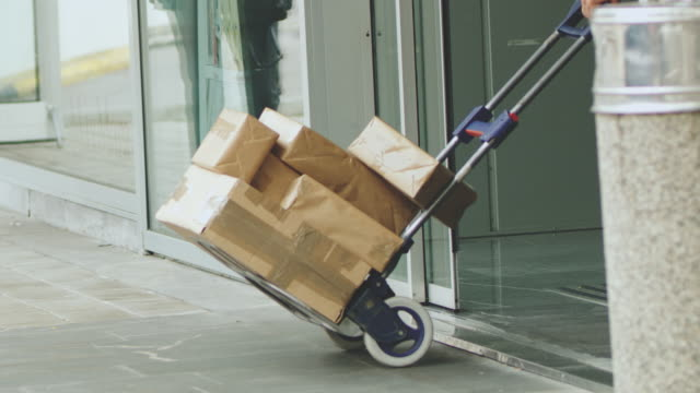 vídeos de stock e filmes b-roll de ms delivery person pulling hand truck with packages through doorway - carrinho de mão carrinho
