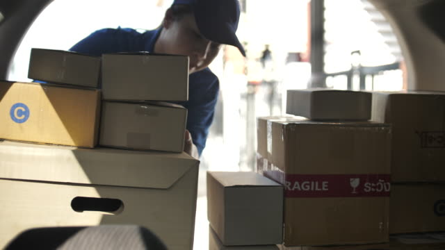 delivery service worker carrying the package for preparing to delivery and walking out of the van, out of delivery - picking up stock videos & royalty-free footage