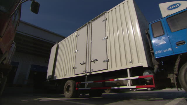 A delivery truck backs up to a loading dock.