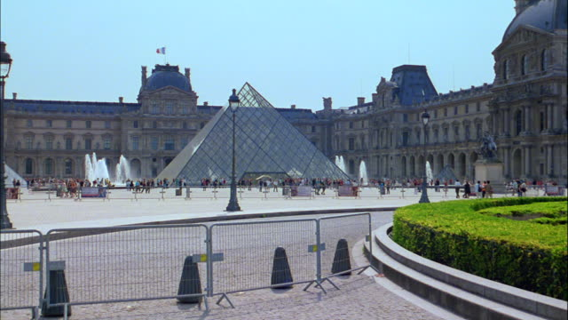 A delivery truck passes the Glass Pyramid in the courtyard of the Louvre Musuem.