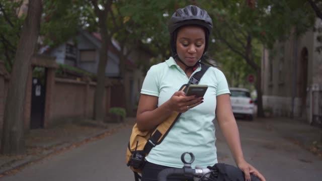vidéos et rushes de femme de livraison ethnicité noire vérifier sur son application mobile emplacement droit pour la livraison - regarder autour de soi