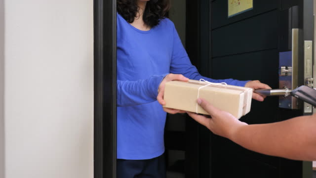 delivery worker delivers packages at home - receiving stock videos and b-roll footage