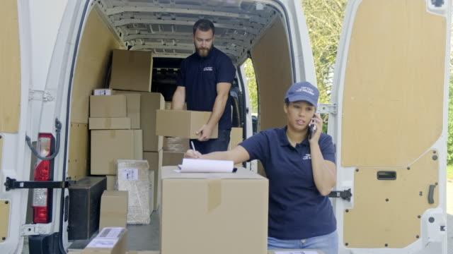 zusteller entladen den lieferwagen - hubwagen stock-videos und b-roll-filmmaterial