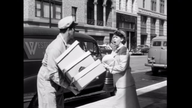 1952 a deliveryman accidently bumps into a woman, eliciting an angry response - human settlement stock videos & royalty-free footage