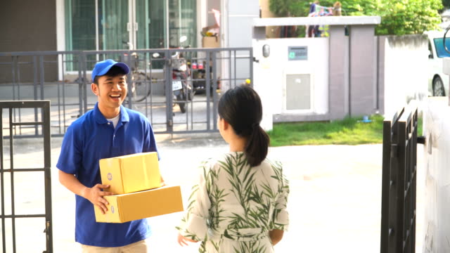 deliveryman deliveries two box at her home - receiving stock videos and b-roll footage