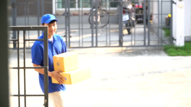 deliveryman feel happy and smile to delivery two box at her home - postal worker stock videos & royalty-free footage