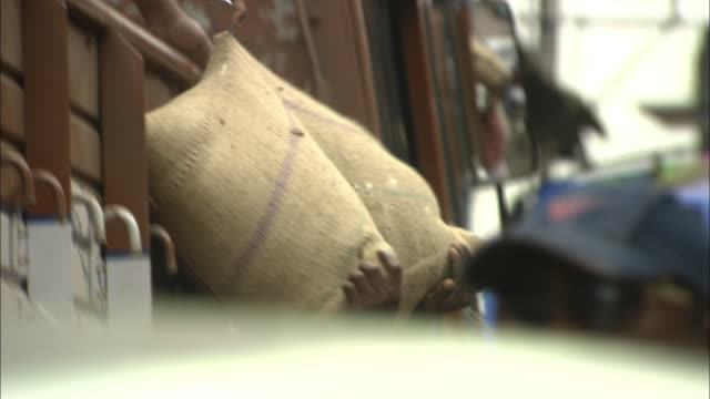 deliverymen unload heavy sacks from a truck in kochi, india. - 荒い麻布点の映像素材/bロール