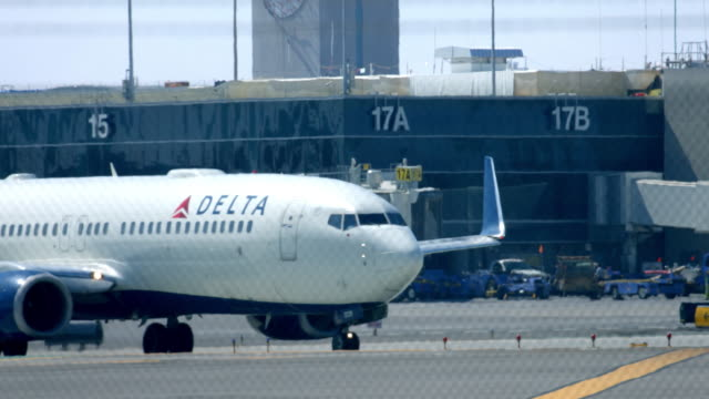 delta airline plane with passengers arrives to lax airport near control tower on march 17 2016 in los angeles california 4k from raw / los angeles... - delta air lines stock-videos und b-roll-filmmaterial