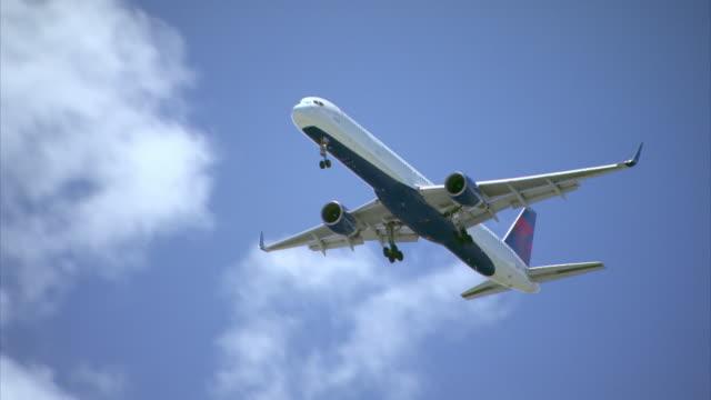 vidéos et rushes de a delta airlines aeroplane flies into a puerto rican airport against a blue sky. - atterrir