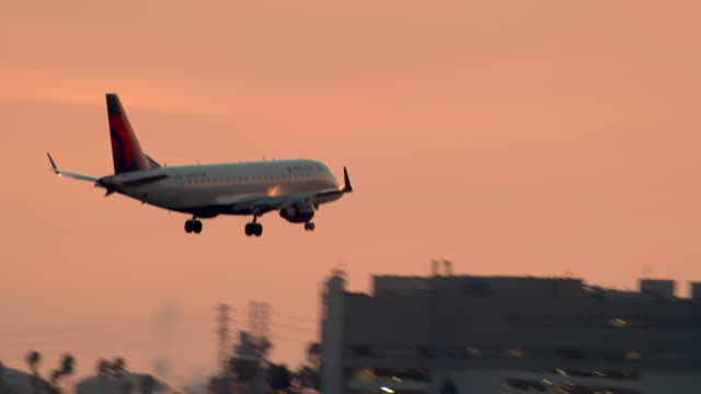 vidéos et rushes de ls pan delta airlines twin engine passenger jet on final approach before landing at lax at dusk passing by el segundo office buildings - avion
