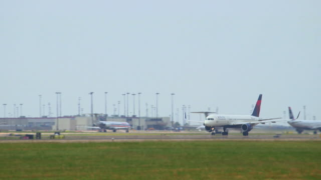 pan delta jetliner taking off with airport  terminal and tower in background/dfw international airport, dallas-fort worth, texas, usa - südwestliche bundesstaaten der usa stock-videos und b-roll-filmmaterial
