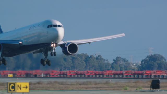 deltas airlines jumbo jet touches down for landing in slow motion, camera tracks landing gear - タッチダウン点の映像素材/bロール