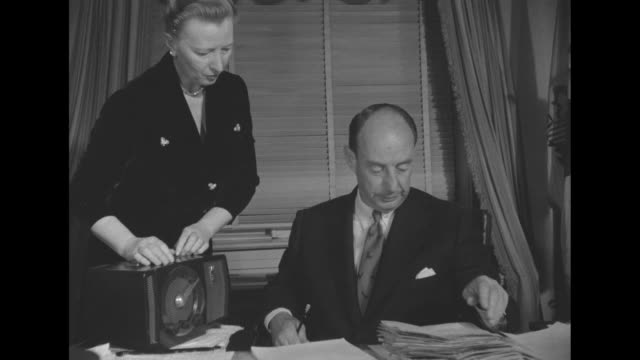 cu democratic presidential candidate adlai stevenson at desk in governor's mansion signs papers secretary hands him more papers / cu stevenson... - governmental occupation stock videos & royalty-free footage