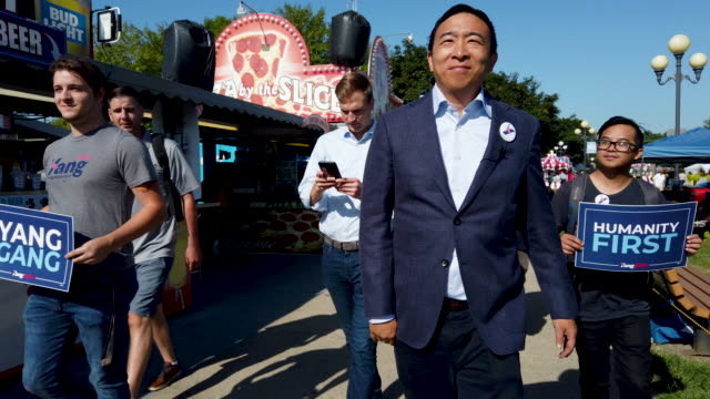 vídeos de stock e filmes b-roll de democratic presidential candidate andrew yang and his staff and supporters walk along grand avenue after arriving at the iowa state fair august 09... - feira agrícola