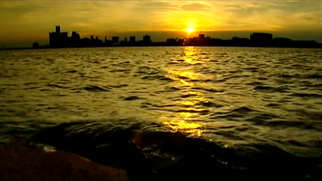 democrats prepare for party convention; usa: michigan: pontiac: ext sunsetting over lake with cityscape silhoutte in background - michigan stock videos & royalty-free footage