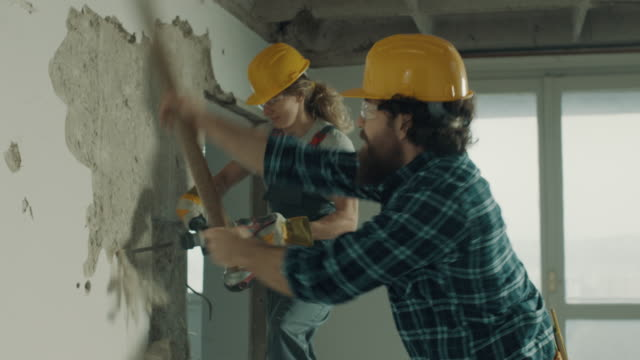 demolishing wall together - construction worker stock videos & royalty-free footage