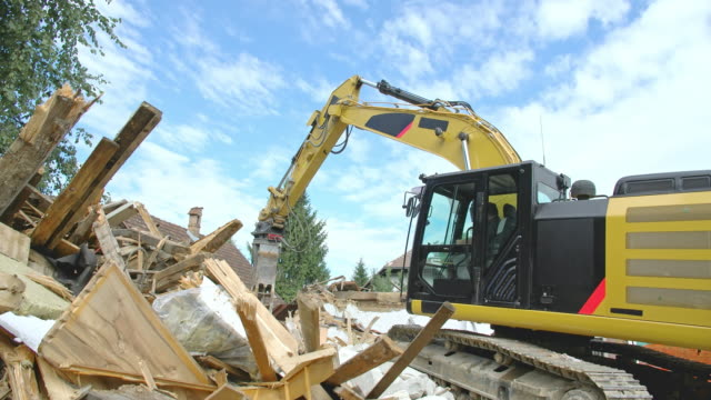 cs demolition excavator piling up the wooden parts of the demolished building - construction vehicle stock videos and b-roll footage