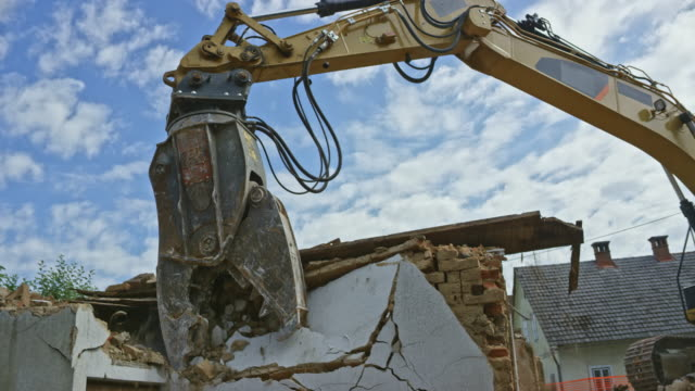 demolition excavator tearing down an old building - demolishing stock videos & royalty-free footage