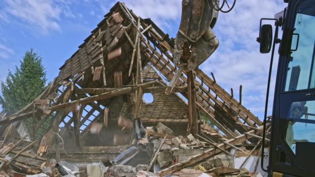 demolition excavator tearing down the roofing and the last standing wall of the old house - last stock videos & royalty-free footage