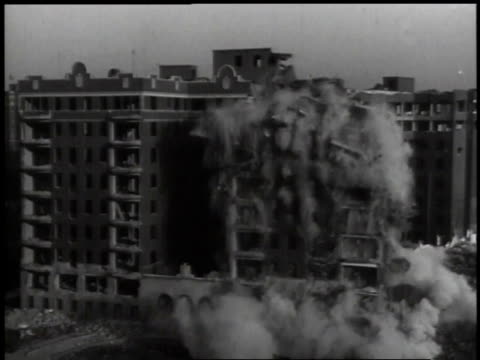 1941 MONTAGE Demolition of building with man pushing detonation device and then building exploding and falling to the ground in smoke and dust / Washington D.C., United States