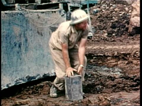 A demolition worker depresses a dynamite plunger