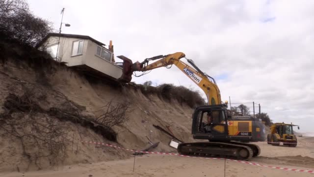 vidéos et rushes de demolition workers have torn down a clifftop home that was on the brink of falling into the sea after a storm caused significant erosion. they used... - érodé