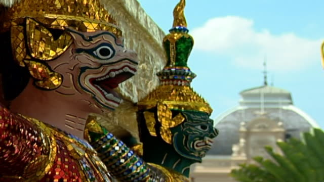 of demon statues at the base of a golden chedi, or spire. the statues are covered with sparkling glass mosaics. - spire stock videos & royalty-free footage