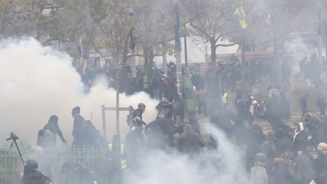 vidéos et rushes de demonstrating with tear gas. place of italy during a protest to mark the first anniversary of the 'yellow vests' movement on november 16, 2109 in... - confrontation