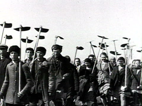 demonstration in countryside, people holding banners, hoes, rakes and shovels, horse drawn carts, tractors audio/ russia - anno 1928 video stock e b–roll