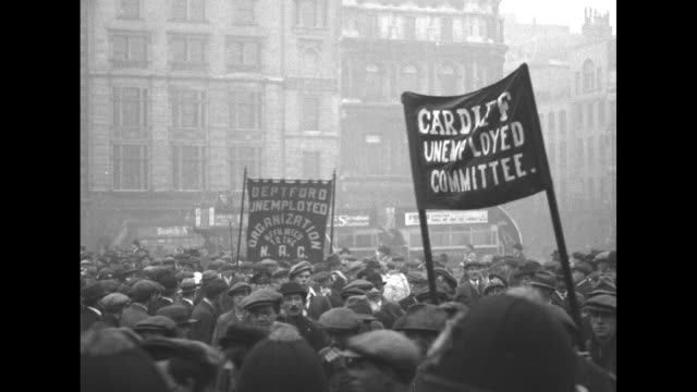 demonstration in london against unemployment / men marching with banners / men on stage / one man giving a speech to crowd / crowd standing on... - newsreel stock videos & royalty-free footage