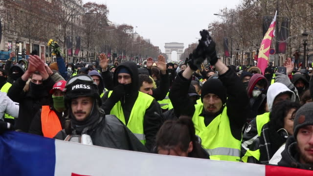demonstration of yellow vests in front of the triumphal arch french flags