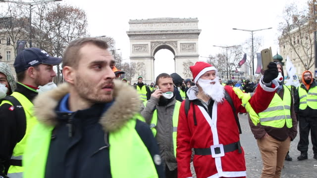 demonstration of yellow vests in front of the triumphal arch man in santa claus - reflective clothing stock videos & royalty-free footage