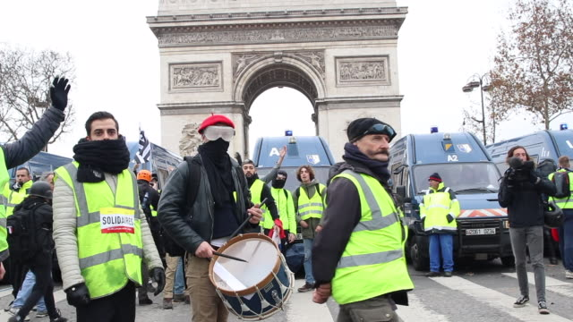 demonstration of yellow vests in front of the triumphal arch man with a beret and a drum Gendarmerie vehicle