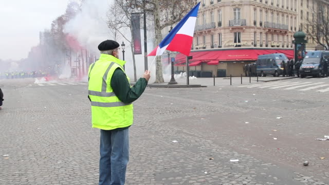 demonstration of yellow vests on the avenue des champs elysées man with french flag in front of the police and gendarmerie - reflective clothing stock videos & royalty-free footage