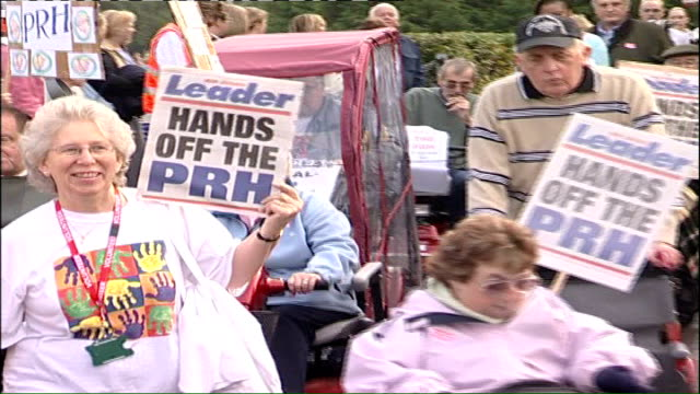 oxfordshire witney ext protestors demonstrating against alleged nhs cuts along on march carrying placards and banners 'hands off the prh' as band... - oxfordshire stock videos & royalty-free footage