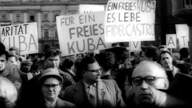 Demonstrations in East Berlin for and against Castro and Cuba shortly before JFK's 'Bay of Pigs' speech / people holding signs