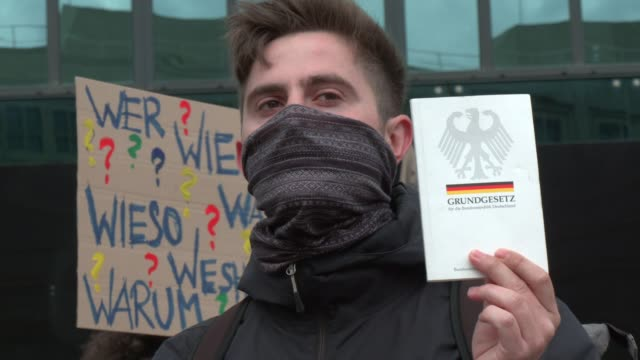 demonstrator holds a copy of germany's basic law, its constitution, as he wears a protective face mask during a protest at alexanderplatz against... - 憲法点の映像素材/bロール