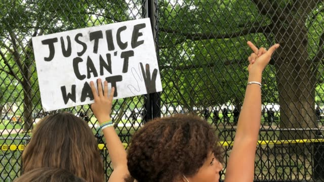 vidéos et rushes de a demonstrator holds a sign saying justice can't wait and another gives a hand gesture while chanting behind the new white house fence to protest the... - clôture