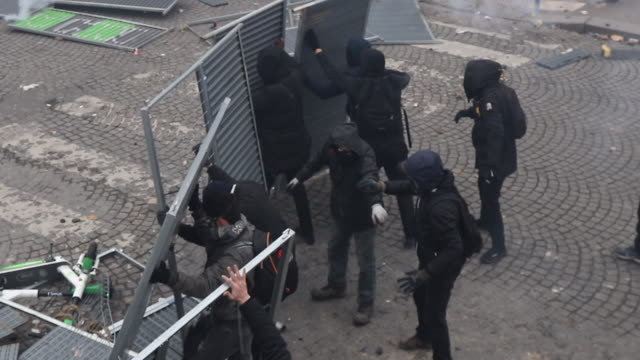 demonstrator throwing stones at police. place of italy during a protest to mark the first anniversary of the 'yellow vests' movement on november 16,... - 公共物破壊点の映像素材/bロール
