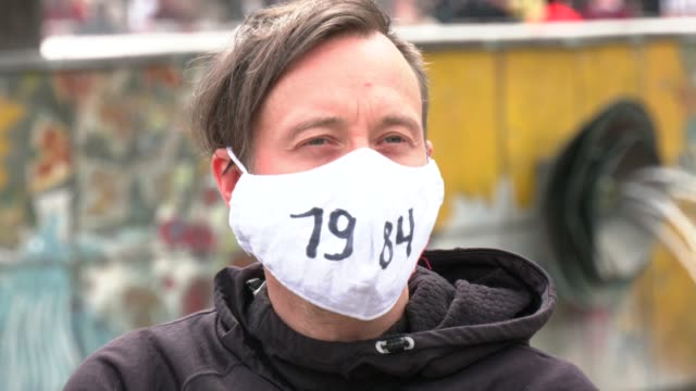 """demonstrator wearing a face mask with the inscription """"1984"""", referring to the novel """"1984"""" by george orwell, which describes a totalitarian... - アレクサンダープラッツ点の映像素材/bロール"""