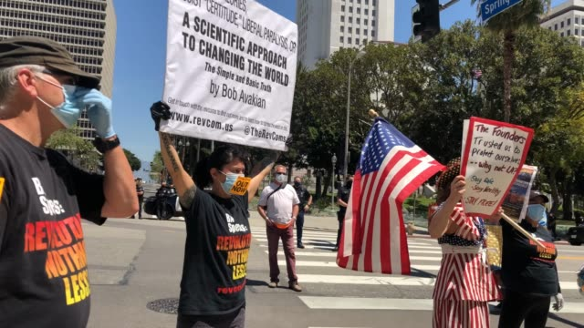 stockvideo's en b-roll-footage met a demonstrator with american flag shouts by counterprotestors during a protest outside city hall calling on california officials to reopen the... - heropening
