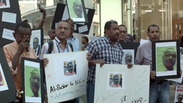 demonstrators at yongedundas square in toronto protest the imprisonment of sudanese activist hisham ali - スーダン点の映像素材/bロール