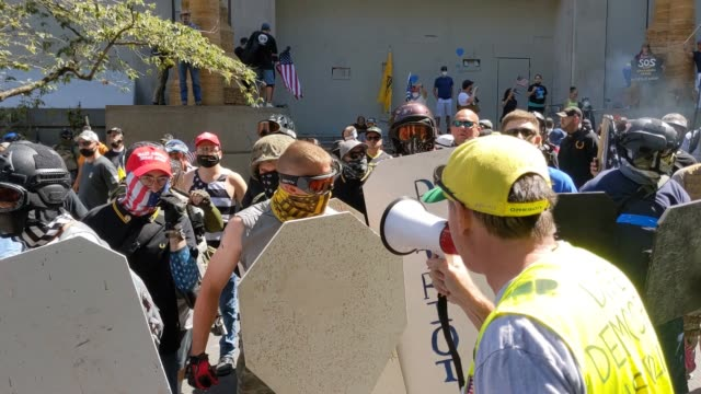 demonstrators behind shields and chant usa as right wing groups and portland anti-police protesters face off in front of the multnomah county justice... - portland oregon stock videos & royalty-free footage